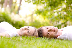 Barnet kopplar ihop det liggande huvudet - - head på gräset Arkivbilder