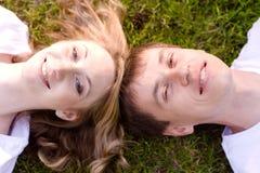 Barnet kopplar ihop det liggande huvudet - - head på gräset Royaltyfria Foton