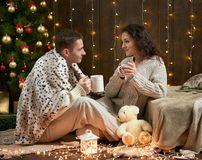 Barnet kopplar ihop drinkte, sitter på golv i mörk träinre med ljus Romantisk afton och förälskelsebegrepp Ferie för nytt år Chr Arkivbilder