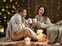 Barnet kopplar ihop drinkte, sitter på golv i mörk träinre med ljus Romantisk afton och förälskelsebegrepp Ferie för nytt år Chr Arkivfoto