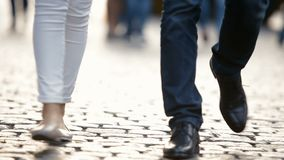 Barnet kopplar ihop, en man, och en kvinna, går runt om staden, längs trottoaren Lägger benen på ryggen närbild stock video