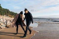 Barnet kopplar ihop förälskad körning i väg från vågor Lyckliga vänner har gyckel på stranden royaltyfri bild