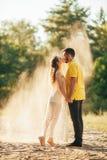 Barnet kopplar ihop förälskade kyssar i skog mot bakgrund av sand royaltyfria bilder