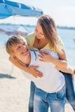 Barnet kopplar ihop förälskat ha gyckel och hoppa på stranden Royaltyfria Bilder