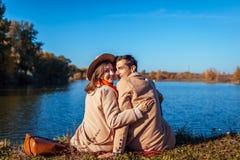 Barnet kopplar ihop förälskat kyla vid höstsjön Lycklig man och kvinna som tycker om naturen och att krama arkivbilder