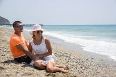 Barnet kopplar ihop förälskat ligga på stranden som tycker om royaltyfri bild