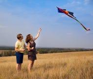 Barnet kopplar ihop förälskat med att flyga en drake på bygd Fotografering för Bildbyråer