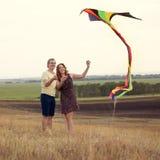 Barnet kopplar ihop förälskat med att flyga en drake på bygd Arkivfoton