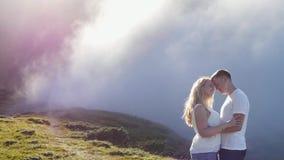Barnet kopplar ihop förälskat på en bergäng på bakgrunden av dimma och solen Royaltyfria Bilder