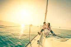 Barnet kopplar ihop förälskat seglar på fartyget med champagne på solnedgången Royaltyfri Fotografi