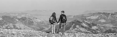 Barnet kopplar ihop fotvandrare som tycker om sikten av bergen Fotografering för Bildbyråer