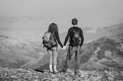 Barnet kopplar ihop fotvandrare som tycker om sikten av bergen Royaltyfri Bild