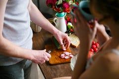Barnet kopplar ihop framställning av nytt mål tillsammans i köket royaltyfri foto