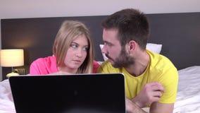 Barnet kopplar ihop genom att använda bärbara datorn, medan ligga i säng hemma, online-shopping stock video