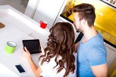 Barnet kopplar ihop genom att använda en minnestavlaPC i köket hemma Arkivbilder