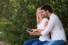 Barnet kopplar ihop genom att använda internet som är utomhus- med den digitala minnestavlan Arkivbild