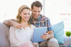 Barnet kopplar ihop genom att använda minnestavlaPC på soffan Royaltyfria Bilder