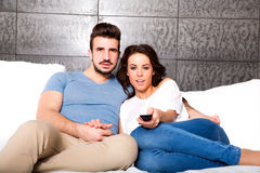 Barnet kopplar ihop hållande ögonen på TV tillsammans på soffan Arkivfoton
