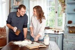 Barnet kopplar ihop i köket som spelar med mjöl arkivbild