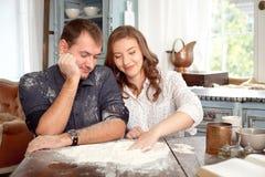 Barnet kopplar ihop i köket som spelar med mjöl Arkivfoto