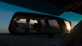 Barnet kopplar ihop i reflexion av den auto spegeln, ser översikten på solnedgången nära vägen arkivbilder