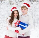 Barnet kopplar ihop i Santa Claus hattar som kramar och rymmer gåvor Arkivbild