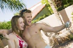 Barnet kopplar ihop i swimwear som fotograferar själv i bakgård Royaltyfria Foton