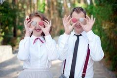 Barnet kopplar ihop innehavet färgade macarons på ögonen arkivfoton