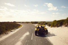 Barnet kopplar ihop körning ner en öppen väg till stranden royaltyfri foto