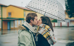 Barnet kopplar ihop kyssande det fria under paraplyet i en regnig dag Arkivbilder