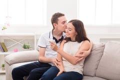 Barnet kopplar ihop lyckligt om resultat av graviditetstestet royaltyfria bilder
