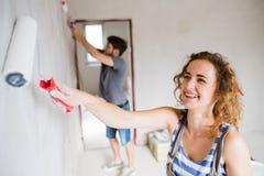 Barnet kopplar ihop målningväggar i deras nya hus Arkivbilder