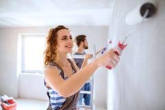 Barnet kopplar ihop målningväggar i deras nya hus Royaltyfri Foto