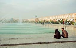 Barnet kopplar ihop möte och samtal nära en springbrunn av den populära imamen Square i Isfahan Arkivfoton