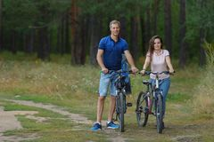 Barnet kopplar ihop med cyklar parkerar in och att cykla på sommardagen arkivfoton