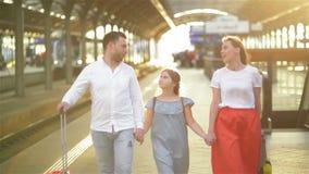 Barnet kopplar ihop med dotterankomster från semestrar Familj som går på plattformen av järnvägsstationen med resväskor Lyckligt lager videofilmer