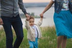 Barnet kopplar ihop med en barndans och en hagyckel i natur - framme av floden Arkivfoto