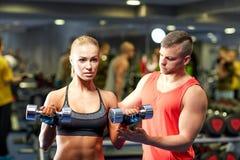 Barnet kopplar ihop med hantlar som böjer muskler i idrottshall Fotografering för Bildbyråer