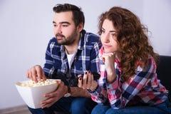 Barnet kopplar ihop med hållande ögonen på film för popcorn på tv Arkivfoto