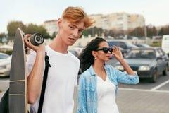 Barnet kopplar ihop med skateboarden som har gyckel på stadsgatan royaltyfri foto