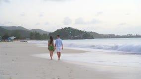 Barnet kopplar ihop på den vita stranden under sommarsemester Den lyckliga familjen tycker om deras bröllopsresa stock video