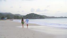 Barnet kopplar ihop på den vita stranden under sommarsemester Den lyckliga familjen tycker om deras bröllopsresa arkivfilmer