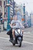 Barnet kopplar ihop på en kall sparkcykel, Amsterdam, Nederländerna royaltyfri fotografi