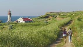 Barnet kopplar ihop på soligt väder går nära kustlinjen med den romantiska fyren på bakgrund tillbaka sikt stock video