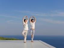 Barnet kopplar ihop praktiserande yoga Arkivfoto