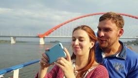 Barnet kopplar ihop resande vid skeppdanandeselfie med mobiltelefonen som ser skott på härlig brobakgrund brigham stock video