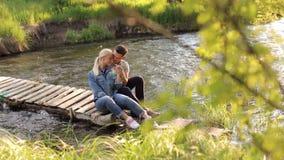 Barnet kopplar ihop sammanträde som omfamnar på bron vid floden stock video