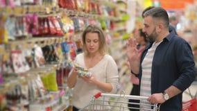 Barnet kopplar ihop shopping i en livsmedelsbutik Lycklig familj som har mycket roliga spendera Time tillsammans Söka efter något stock video