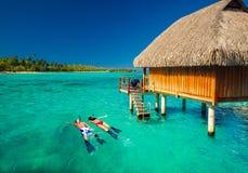 Barnet kopplar ihop snorkling från koja över den tropiska lagun royaltyfria bilder