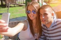 Barnet kopplar ihop tonåringar som utomhus ler och tar selfie fotografering för bildbyråer
